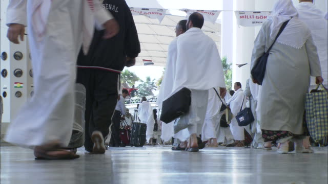 pilgrims and travelers walk through the hajj terminal. - saudi arabia stock videos and b-roll footage