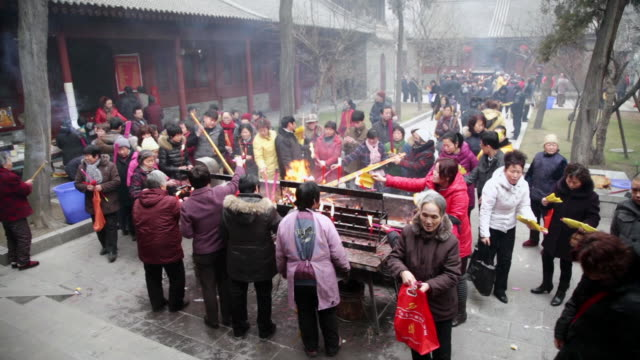 MS Pilgrims burning joss sticks and candles to praying for good luck and burn ghost money to praying for dead relatives during Chinese Lunar New Year at Buddhist temple / xi'an, shaanxi, china