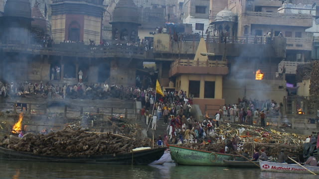 Pilgrims carry a body to a funeral pyre on the edge of the Ganges.