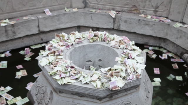 cu zo tu pilgrims circle round wishing well to touch stone lion and drop money pray for good luck during chinese lunar new year at taoist temple / xi'an, shaanxi, china - wishing well stock videos & royalty-free footage