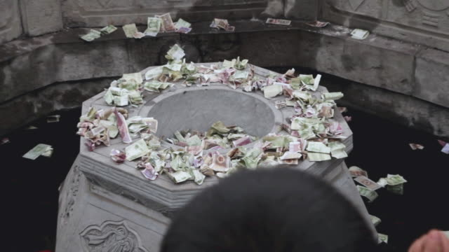 cu zo pilgrims circle round wishing well to touching stone lion and drop money pray for good luck during chinese lunar new year at taoist temple /xi'an, shaanxi, china - wishing well stock videos & royalty-free footage