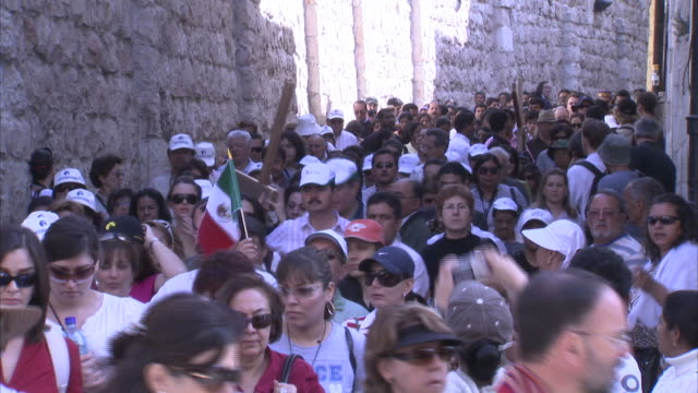 stockvideo's en b-roll-footage met pilgrims crowd the narrow street as they walk in procession. available in hd - bedevaart