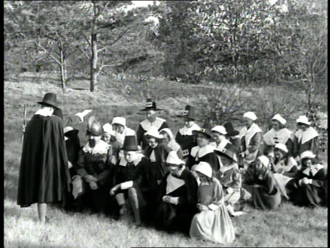 Pilgrims in Massachusetts kneel in a field and pray during a 1660s era reenactment