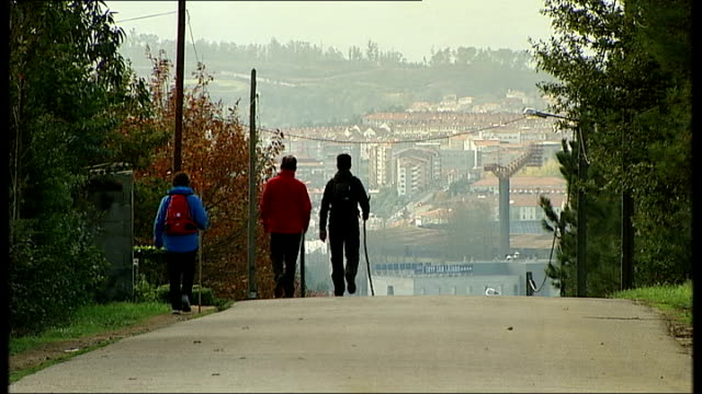 pilgrims in santiago de compostela pilgrims along road towards and past camera / various of pilgrims along road towards city centre - pilgrim stock videos & royalty-free footage