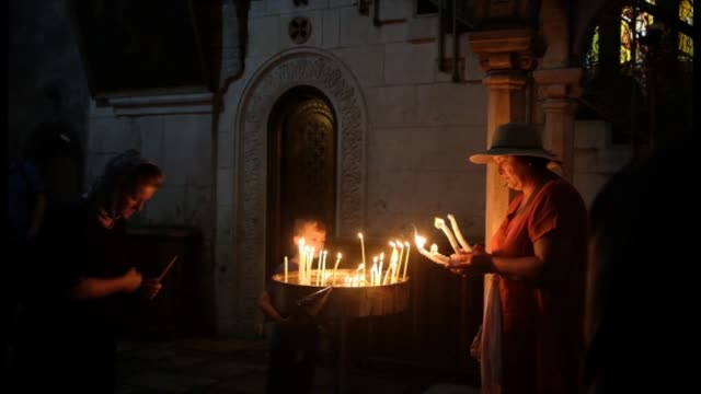 pilgrims light candles in the church of the holy sepulcher on july 09 2018 in jerusalem old city israel - spiritualità video stock e b–roll