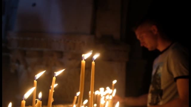 pilgrims light candles in the church of the holy sepulcher on july 09, 2018 in jerusalem old city, israel. - gerusalemme est video stock e b–roll