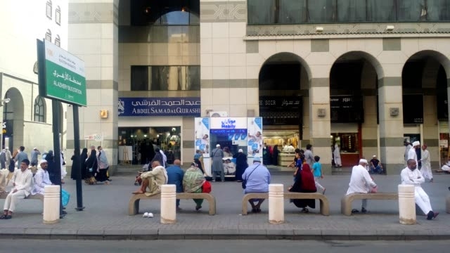 pilgrims or people sitting on bus station (stop) benches and waiting for bus near prophet's mosque. - サウジアラビア点の映像素材/bロール