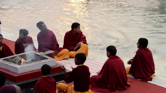 ms pilgrims performing havan at ganges river bank / rishikesh, uttarakhand, india - 僧衣点の映像素材/bロール