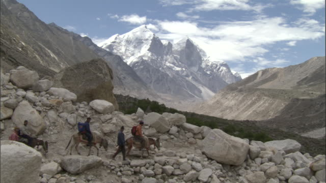 stockvideo's en b-roll-footage met pilgrims ride donkeys across rocky landscape, tapovan, india available in hd. - bedevaart