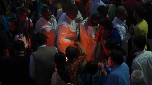 vídeos de stock e filmes b-roll de pilgrims take blessings from a sacred holy fire from a hindu priest in haridwar - benção