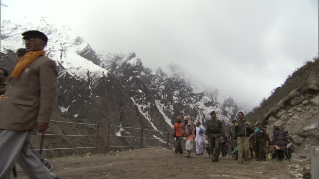 Pilgrims walk along path playing instruments, Kedarnath, India Available in HD.