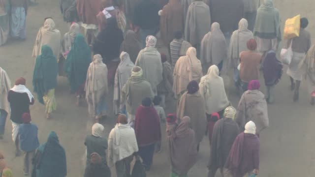 MS, CS, Pilgrims walking on dirt road, rear view, Allahabad, Uttar Pradesh, India