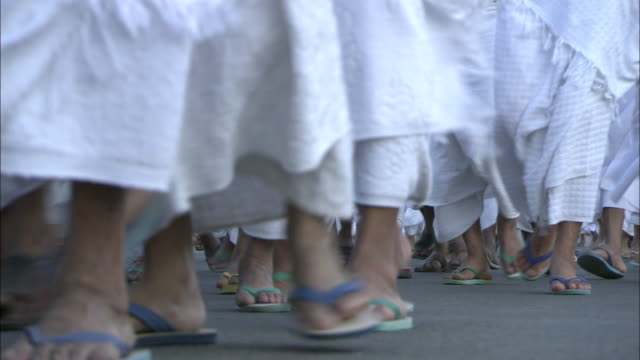 Pilgrims wearing sandals and robes walk together.