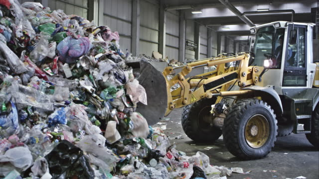 cs piling up plastic waste in a recycling facility - vehicle scoop stock videos and b-roll footage