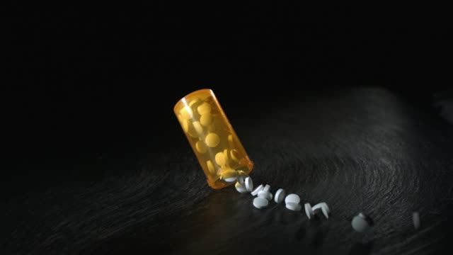 SLO MO CU Pill bottle falling and hitting surface, New York State, USA