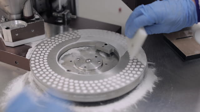 pill encapsulation machine - scraping excess powder from the rotary disc - excess stock videos & royalty-free footage