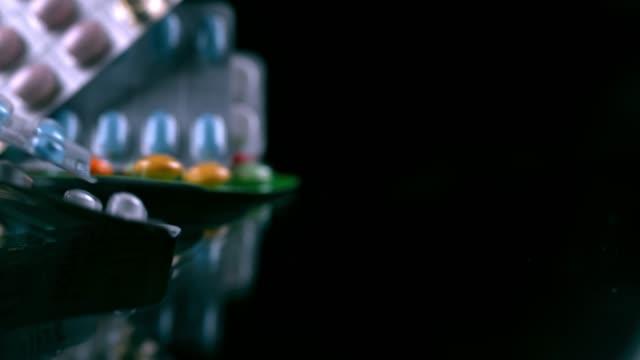 黒い表面に落ちるスローモーションの丸薬 - サプリメント点の映像素材/bロール
