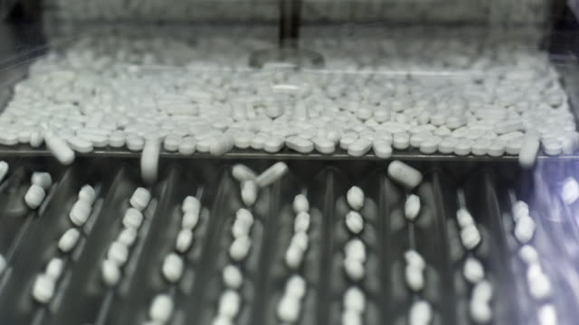cu pills filling into rows at pharmaceutical manufacturer / ratchathewi, bangkok, thailand - medikament stock-videos und b-roll-filmmaterial