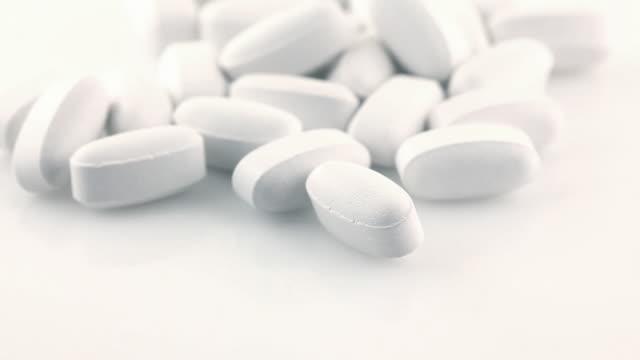 vídeos de stock, filmes e b-roll de pílulas no branco - enfoque de objeto sobre a mesa