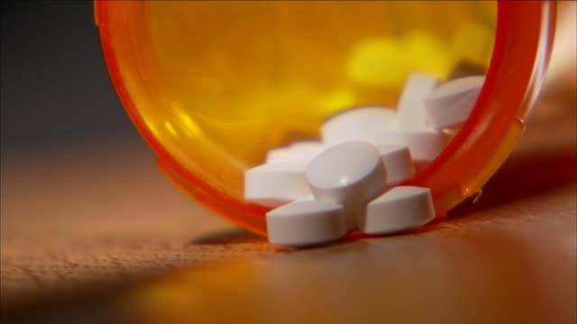 vídeos de stock, filmes e b-roll de pills spill out of a prescription bottle. - prescription medicine