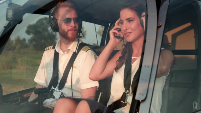 pilot and female passenger inside helicopter giving thumbs up - helicopter tour stock videos and b-roll footage