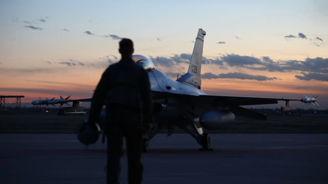 ws f-16 pilot approaching f-16 fighter jet at sunset, aurora, colorado, usa - luftwaffe stock-videos und b-roll-filmmaterial