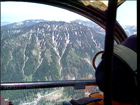 pilot at controls of helicopter air view over mountains air to air army helicopter in flight over mountains air view mountain valley showing river - television show stock videos & royalty-free footage