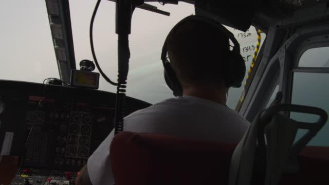 pilot at controls of helicopter over shallow tropical sea, uae - captain stock videos & royalty-free footage