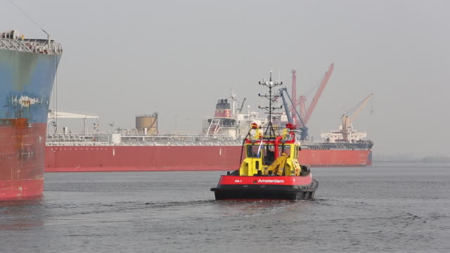 a pilot boat in front of an oil tanker unloading oil at an oil terminal in amsterdam, netherlands. - tanker stock videos & royalty-free footage