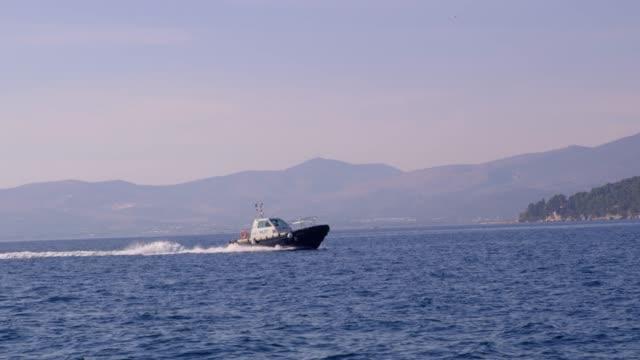 barca pilota 4k che si muove sull'oceano blu soleggiato, in tempo reale - sunny video stock e b–roll