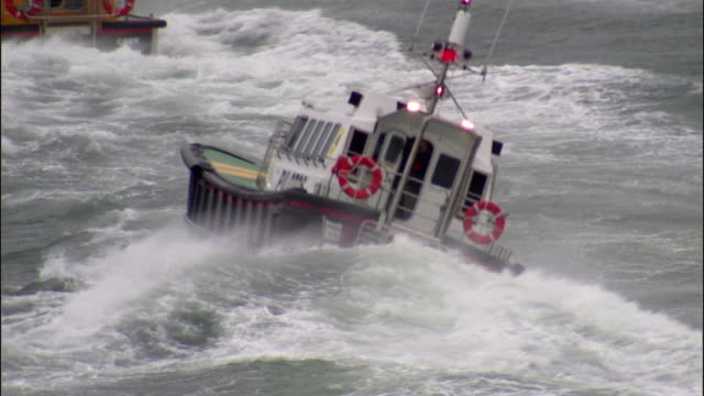 MS POV Pilot boat moving speedily through huge waves in ocean during storm / County Cork, Munster, Ireland