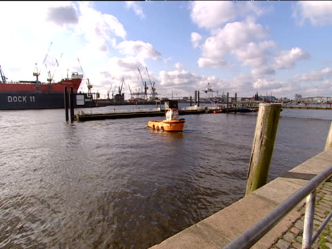 pilot boat reverses and leaves harbour cranes and container ship in background hamburg - langsam stock-videos und b-roll-filmmaterial