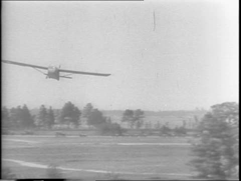 a pilot brings his plane at an angle / he lands safely in the field / the nose dips into the ground and slows the plane / soldiers jump out of the... - anno 1943 video stock e b–roll
