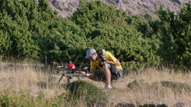 Pilot Überprüfung Drohne vor Flug auf sonnigen Hügel