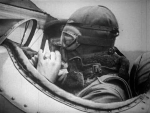 b/w 1929 pilot connecting oxygen tube to mask in airplane cockpit for high elevation flight / dc - oxygen mask stock videos & royalty-free footage