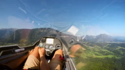 POV Pilot controlling the glider while being towed into the air by a light plane on a sunny day