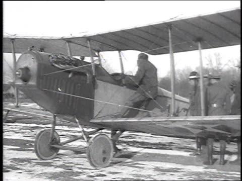 stockvideo's en b-roll-footage met pilot descending from biplane / ground crew standing around a biplane - chillicothe