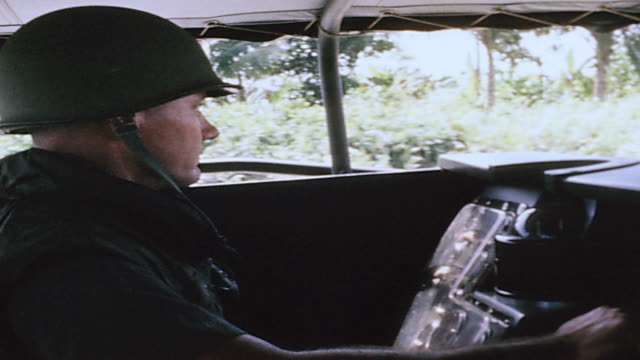 vídeos de stock, filmes e b-roll de pbr pilot driving the boat and gunner manning twinmounted 50 caliber machine guns facing riverbank flowing past / vietnam - formato letterbox
