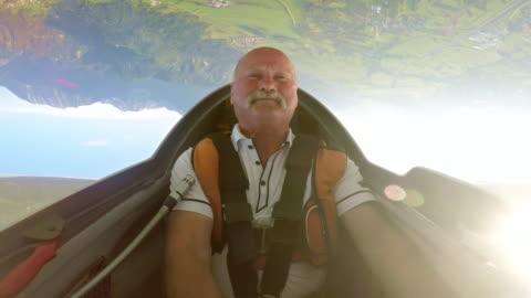 vídeos y material grabado en eventos de stock de piloto de ld disfrutando de la boca hacia abajo en su planeador sobre el campo soleado - deporte de riesgo