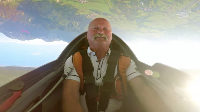 ld pilot enjoying the upside down position in his glider above the sunny countryside - glider stock videos & royalty-free footage