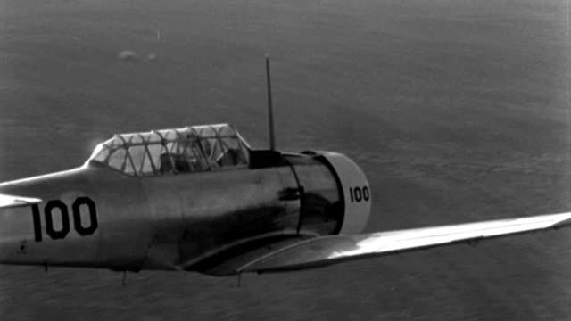 vídeos de stock, filmes e b-roll de a pilot flies a wwii trainer aircraft over farmland. - segunda guerra mundial