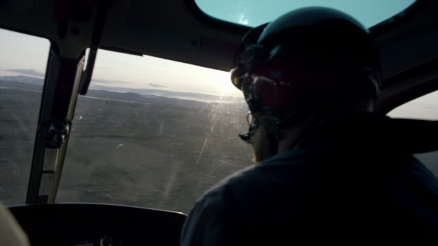 pilot flies helicopter across volcanic landscape - expertise stock videos & royalty-free footage