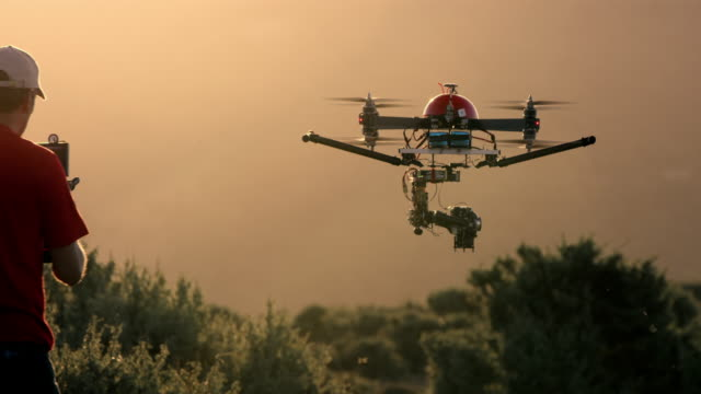 SLO MO UAV Pilot flying drone with camera at sunset