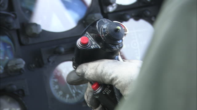 a pilot in a cockpit holds a joystick to control a helicopter. - aeroplane stock videos & royalty-free footage