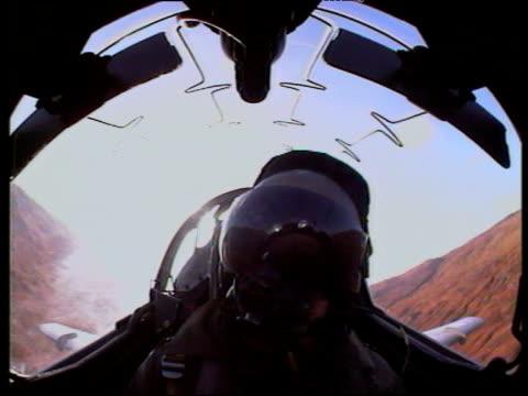 Pilot in military jet cockpit flying landscape in background