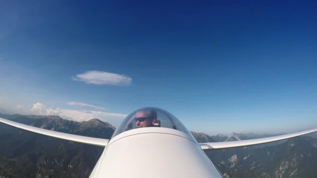 vídeos de stock e filmes b-roll de ld pilot in the glider looking at the beautiful countryside below him - só um homem maduro