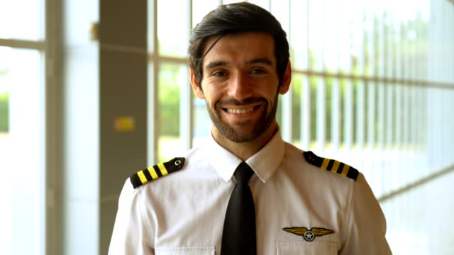 pilot in uniform standing in the airport - captain stock videos & royalty-free footage