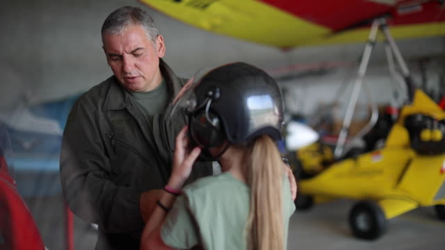 pilot instructor and little girl in the airplane hangar - airplane hangar stock videos & royalty-free footage