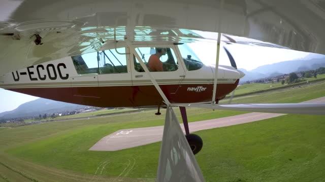 ld-pilot landung ein kleinflugzeug auf dem grasbewachsenen flugfeld bei sonnenschein - propeller stock-videos und b-roll-filmmaterial