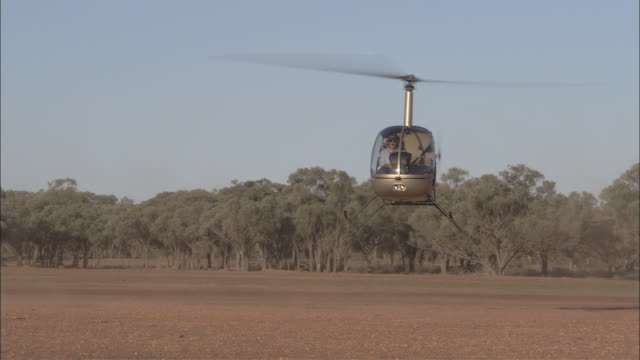 a pilot lands a helicopter in a dusty field. - helicopter landing stock videos & royalty-free footage